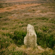 A lonely standing stone approximately 0.8m tall. Danby Beacon in the background